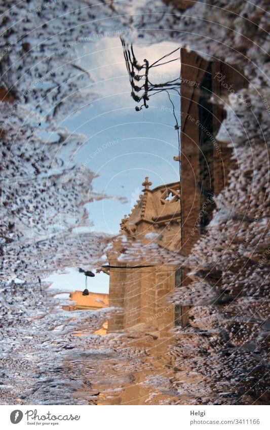 Teil einer Kirche spiegelt sich in einer Pfütze Spiegelung Gebäude Gebäudeteil Gemäuer Kreuz alt historisch Stein Gehweg Wasser Himmel Reflexion surreal