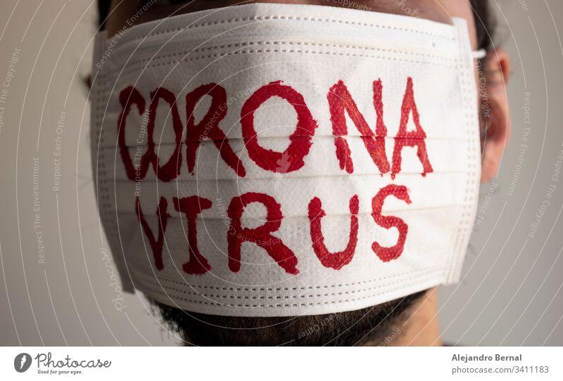 Einem CORONAVIRUS-Patienten mit Bart wurde eine weiße Gesichtsmaske mit roter CORONAVIRUS-Beschriftung angelegt. Konzept-Fotografie COVID-2019 2019-ncov wach