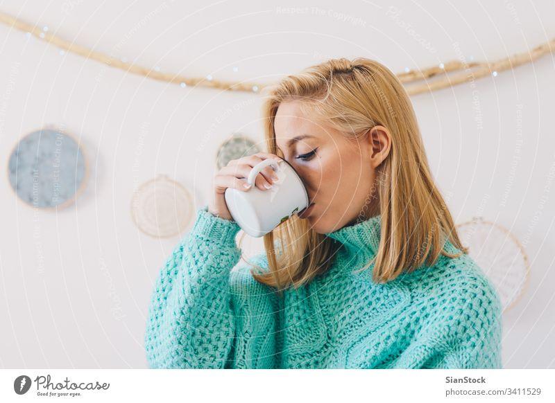 Junges hübsches Mädchen beim Kaffeetrinken Frau Tee jung Tasse Pullover blond Morgen Porträt Glück schön Wand Traumfänger Sonntag Frauen heimwärts Lifestyle