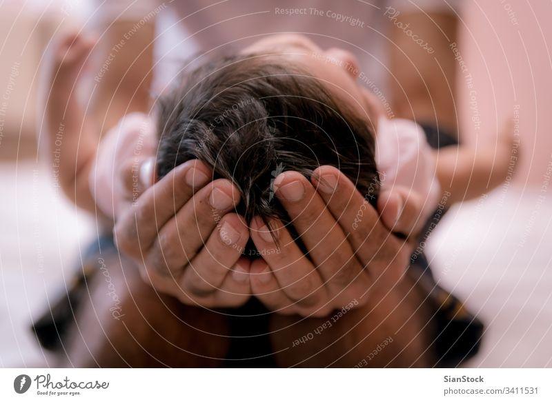 Der Vater hält den Kopf seines Neugeborenen in den Händen, ganz nah. Baby Beteiligung neugeboren niedlich Hand Kind Kaukasier Pflege Kindheit Unschuld schön