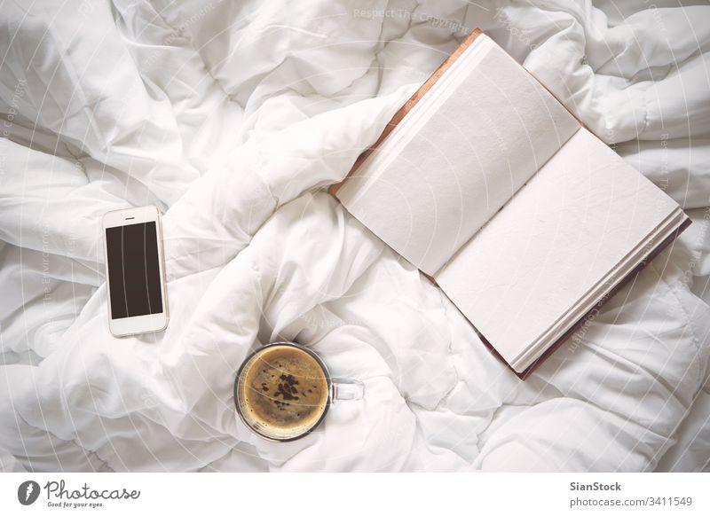 Eine Tasse Kaffee, ein altes Notebook und ein Smartphone auf dem Bett, weiß Laptop Buch Morgen Decke heimwärts Raum Schlafzimmer Licht schön Lichter vereinzelt