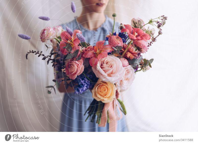 Junge Frau in einem hellblauen Kleid mit einem Blumenstrauß in der Hand. Romantisches Konzept. Mädchen weiches Licht schön altehrwürdig Hochzeit weiß jung