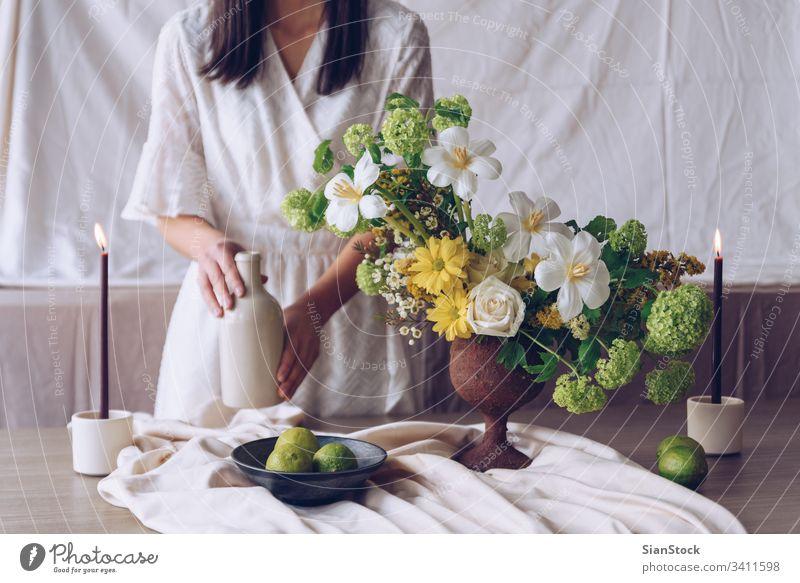 Frau hält Flasche. Stilleben mit Blumenkonzept Tisch jung Kaukasier Halt Beteiligung Hände Hand Kleid weiß Vase brünett Kerzen Kalk Blumenstrauß