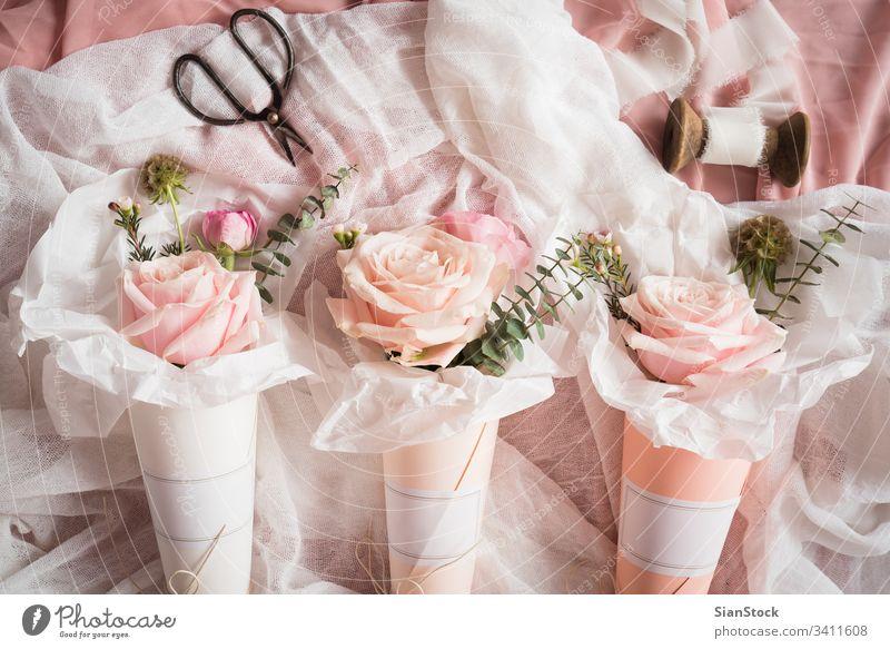 Blumensträuße in Papierkegeln Zapfen Kegel weiß Kornetts Roséwein Rosen Pastell Hintergrund Blumenstrauß vereinzelt Valentinsgruß Tag rosa grün Frühling geblümt