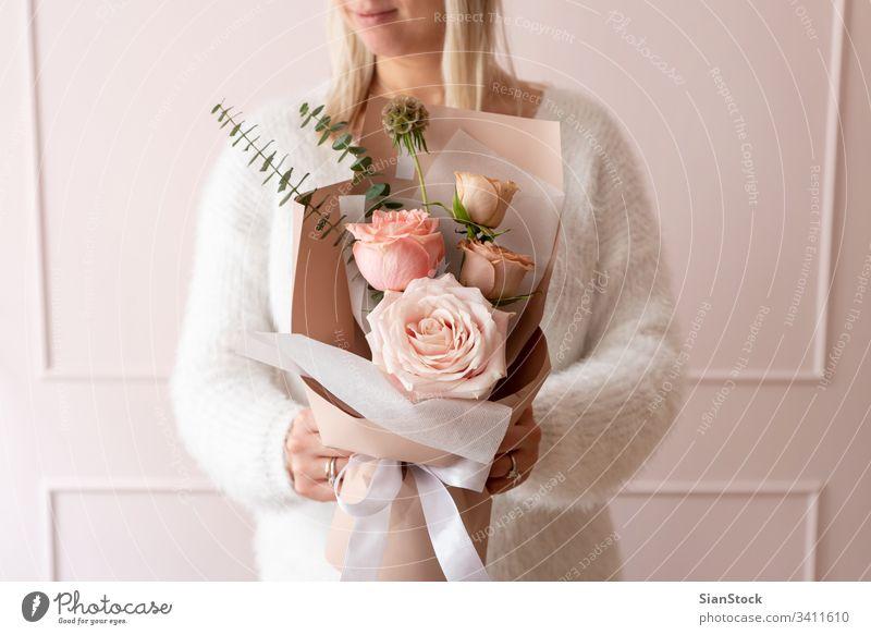 Frau hält einen Rosenstrauß Blumen Blumenstrauß Hand Beteiligung schön Halt Hintergrund geblümt weiß Geschenk Geben frisch Frühling rosa Roséwein Tag Schönheit