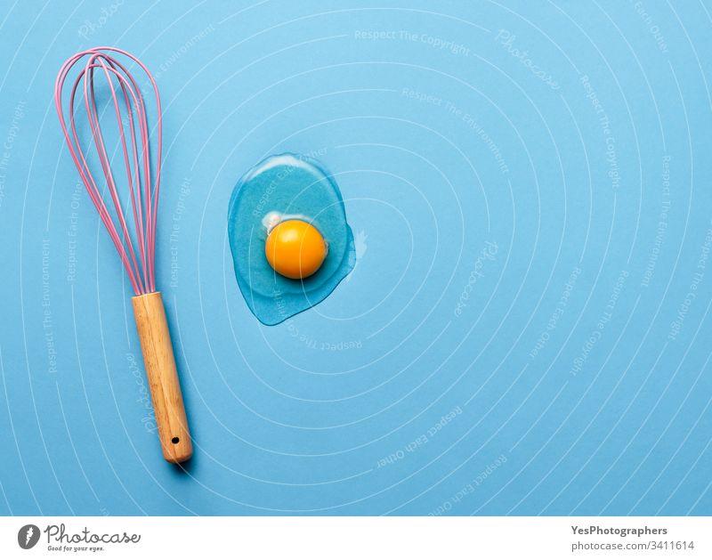 Backkonzept mit Schneebesen und Eigelb backen blau farbenfroh Konzept Essen zubereiten flache Verlegung Lebensmittel Bestandteil Küche Küchengeräte sehr wenige