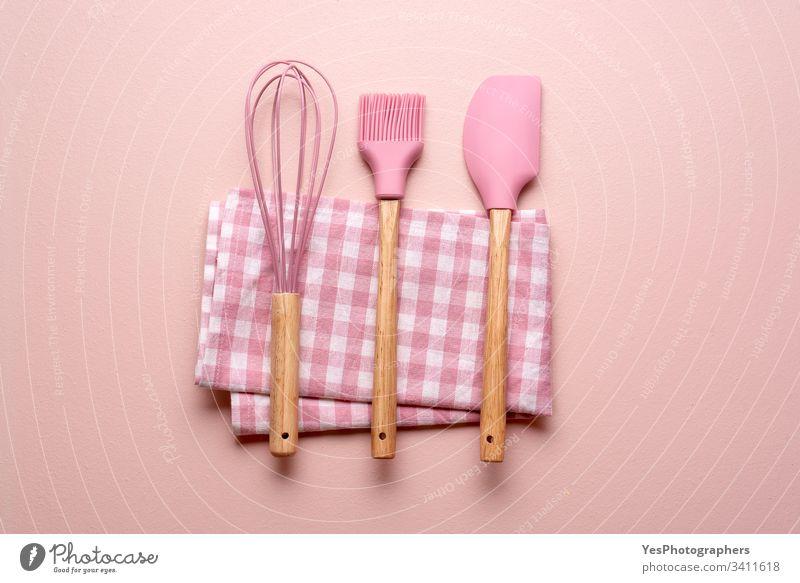 Küchenutensilien auf einem rosa Tisch. Bunte Backwerkzeuge backen Sauberkeit farbenfroh Konzept Essen zubereiten flache Verlegung Haushalt Küchengeräte