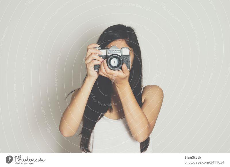 Frau fotografiert mit einer alten Kamera Fotokamera Hintergrund weiß altehrwürdig vereinzelt retro Fotografie Porträt schön Lifestyle Person attraktiv hübsch