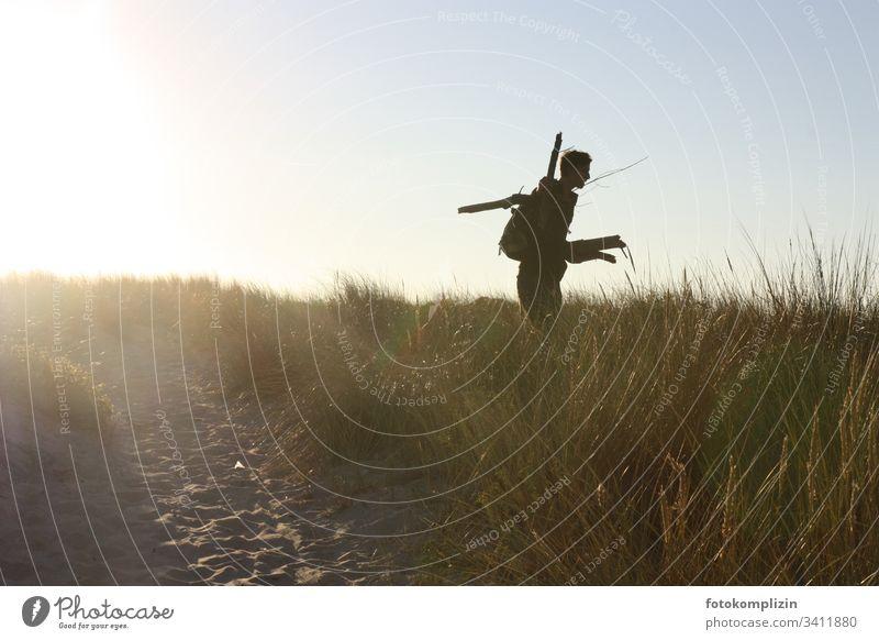 Silhouette eines jungen Manns in einer Stranddüne Feuerholz Düne Dünen Dünengras Ferien & Urlaub & Reisen Holz sammeln freiheitsliebend Abendlicht Abenteurer