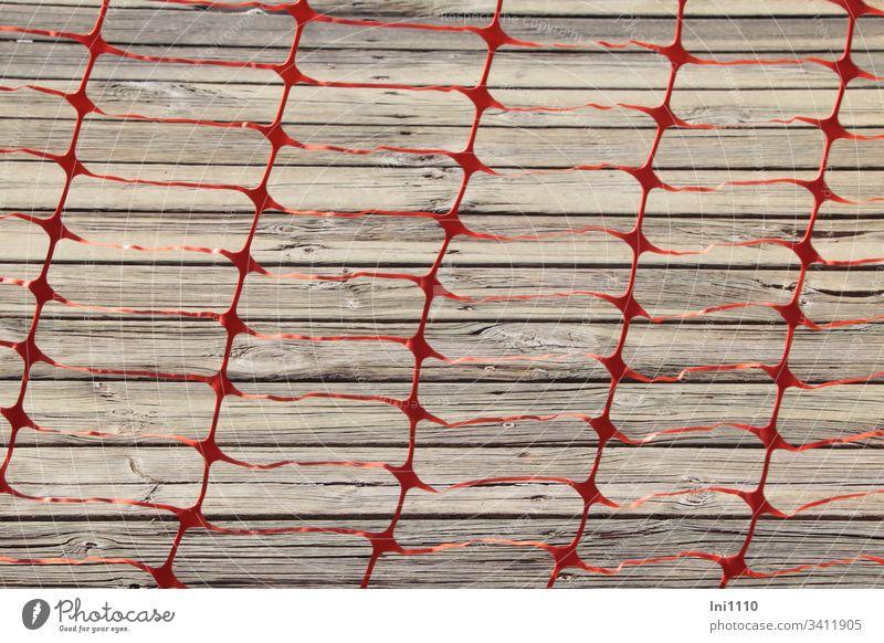 Folienband rot als Gitter ausgestanzt versperrt Durchgang zum grauen Holzsteg Plastik Kunsttofffolie stanzen Absperrung Warnung betreten verboten Gefahr Zaun