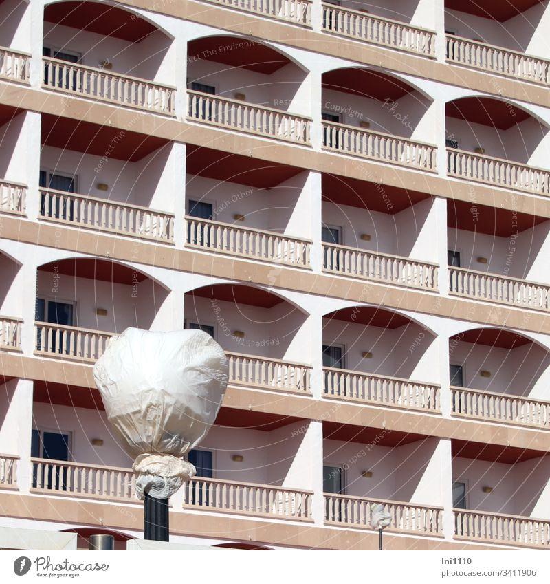"""weiß """"Verhülltes"""" mit Stange vor den Balkonen einer Hochhausfassade weiße Folie Hotelfenster Pension noch keine Saison Frühling Mallorca Terrakotta Sonnenlicht"""