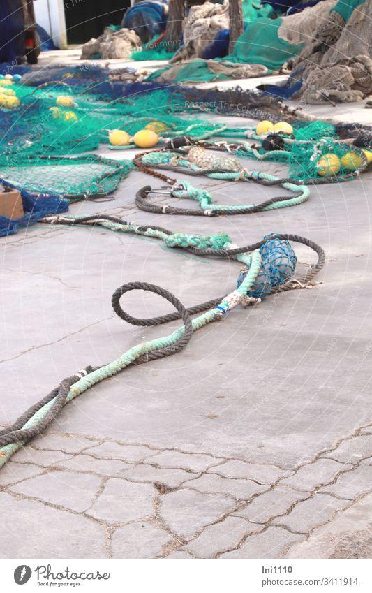 Seilschaft | bunte Fischernetze mit dicken farbigen Seilen und Fischerkugeln liegen auf Kaimauer Meeresfarben Taue ausbreiten blau türkis gelb Schlaufe