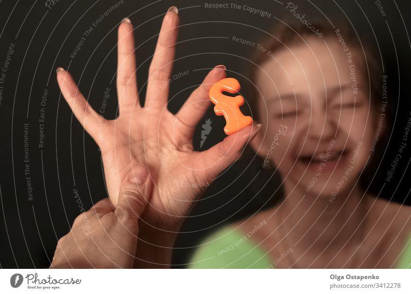 Das Mädchen hält den Buchstaben F. in der Hand.  Alphabet/ Familienkonzept. Buchstabe F Freude Freundschaft gegenseitige Unterstützung Lächeln Nahaufnahme