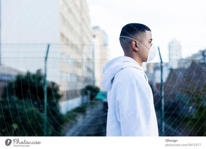 Seitenansicht eines jungen Mannes, der eine Gesichtsmaske zum Schutz vor übertragbaren Infektionskrankheiten und zum Schutz vor Grippe oder Coronaviren an einem öffentlichen Ort trägt.