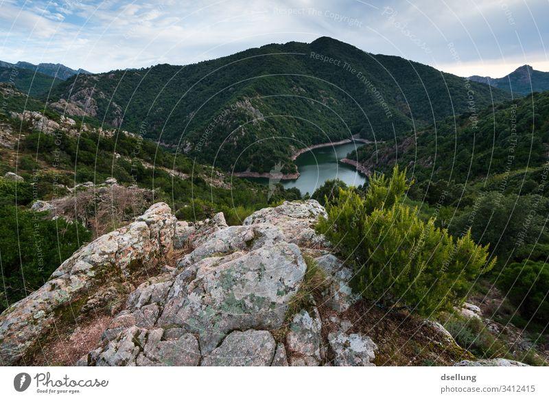 Aussicht auf See und grüne Berge mit Felsen im Vordergrund Wald Sträucher Himmel Wolken Berge u. Gebirge Hügel Landschaft Natur Baum Gras Wiese Außenaufnahme