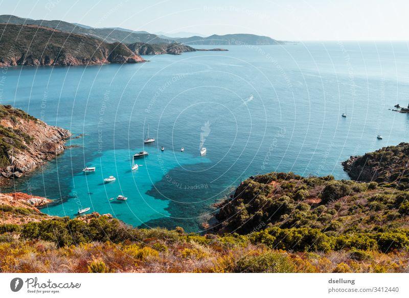 Türkises Meer mit Schiffsverkehr von einer Halbinsel aufgenommen mit Gebirgsarmen türkis blau grün braun Landschaft Urlaubsstimmung Korsika Bootsfahrt Himmel