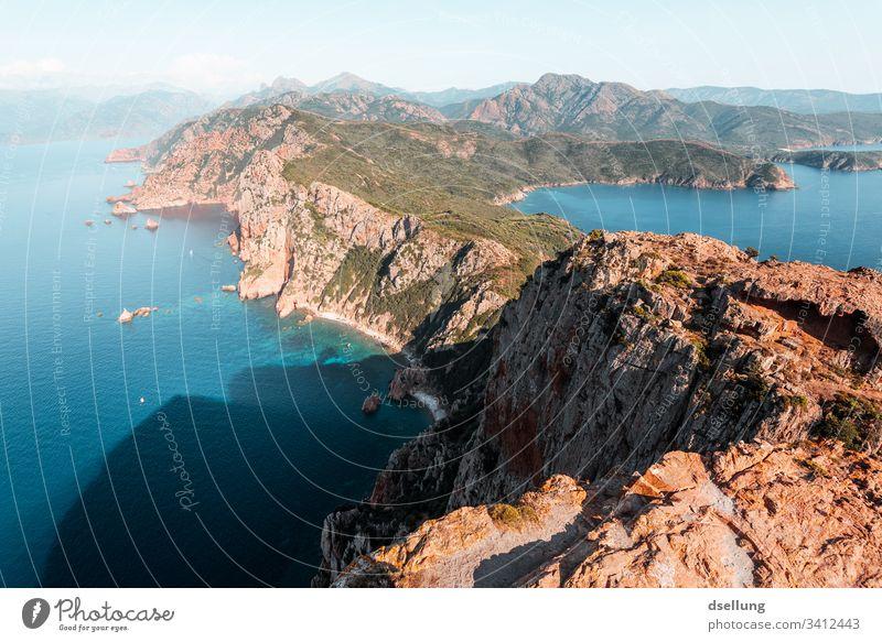 Türkis blaues Wasser mit Felsen arm im Vordergrund Perspektive Farben Kontrast Menschenleer Farbfoto ästhetisch Außenaufnahme türkis grün braun Dämmerung