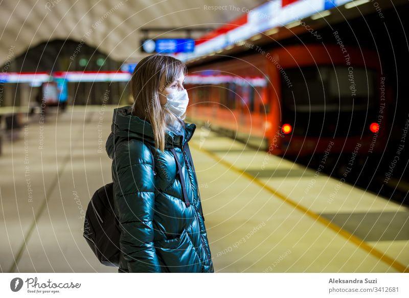 Frau im Wintermantel mit Schutzmaske auf dem Gesicht in der U-Bahn-Station stehend, auf den Zug wartend und besorgt schauend. Präventivmaßnahmen an öffentlichen Plätzen von Epidemiegebieten. Finnland, Espoo