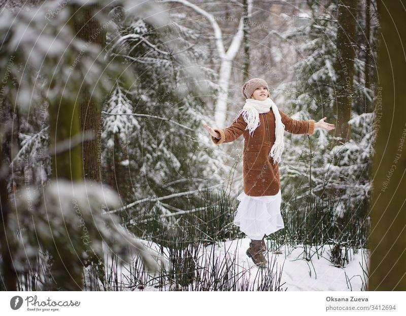 Ein 7-jähriges Mädchen in einem braunen Schafsfellmantel geht im Wald spazieren. Konzept der Jahreszeiten, ein Wintermärchen. Schnee, Bäume. Baby Hintergrund