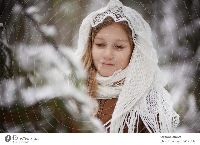 Ein 7-jähriges Mädchen in einem braunen Schafsfellmantel im Winterwald. Konzept der Jahreszeiten, ein Wintermärchen. Schnee, Bäume. Baby Hintergrund schön