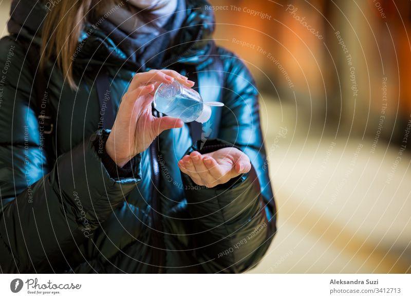 Frau im Wintermantel mit Schutzmaske auf dem Gesicht in der U-Bahn-Station stehend, mit Handdesinfektionsmittel, besorgt schauend. Präventivmaßnahmen an öffentlichen Plätzen von Epidemiegebieten. Finnland, Espoo