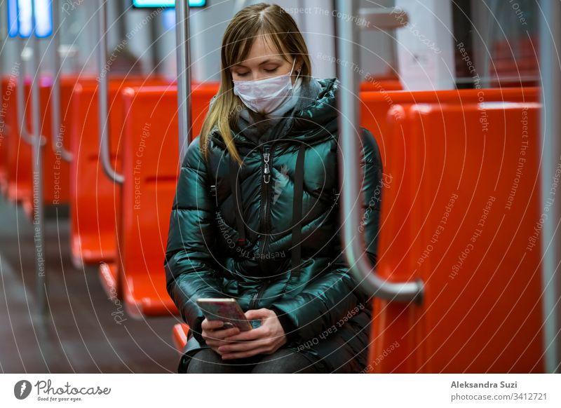 Frau im Wintermantel mit Schutzmaske auf dem Gesicht steht im U-Bahn-Wagen, telefoniert und sieht besorgt aus. Präventivmassnahmen an öffentlichen Orten von Epidemiegebieten. Finnland, Espoo