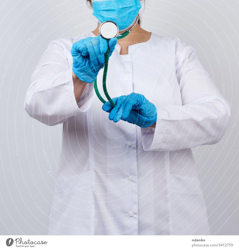 Medizinerin in weißem Mantel und Maske, mit blauen medizinischen Latexhandschuhen Erwachsener Pflege Kaukasier prüfen Klinik Konzept Arzt Gerät Frau Mädchen