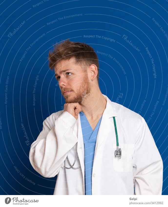Attraktiver Arzt mit weißem Laborkittel auf blauem Hintergrund Uniform Gesundheit überblicken beunruhigt Sorge nachdenklich besinnlich Denken