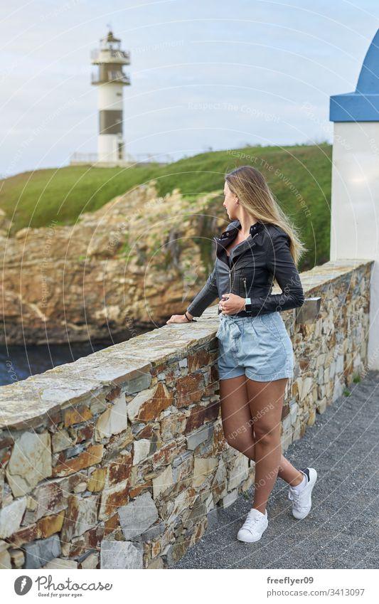Junge Frau mit dem Leuchtturm Illa Pancha in Ribadeo MEER Lugo Galicia Felsen Natur Küste Landschaft Historie Klippe Wasser europa historisch winken blau