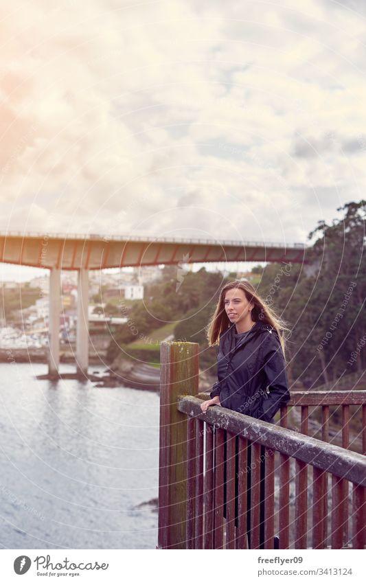 Junge Frau, die von einem Aussichtspunkt aus das Meer betrachtet reisen Brücke Architektur Wasser Touristik Meerblick urban blau Spanien Landschaft hölzern