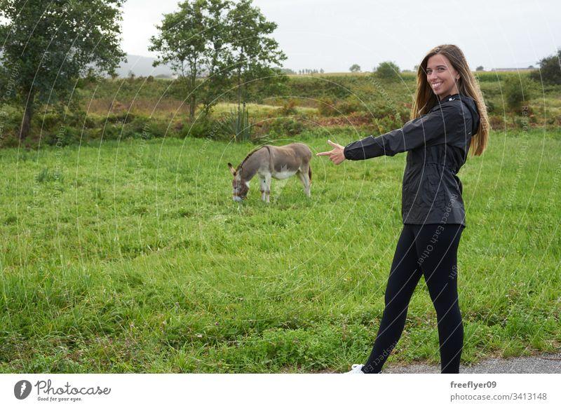 Junge Frau mit einem Esel auf einer Wiese Bauernhof im Freien Lebensmittel Nachkommen Säugetier füttern Aussehen Nutztier niedlich Natur ruhen grün Essen Kopf