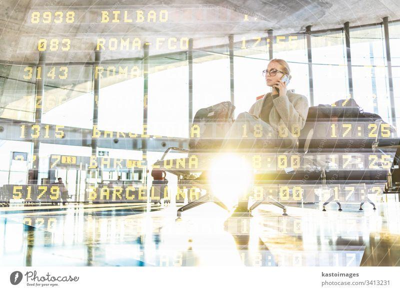 Eine weibliche Reisende, die mit ihrem Handy telefoniert, während sie an den Abfluggates im Flughafen-Terminal auf das Einsteigen in ein Flugzeug wartet. reisen
