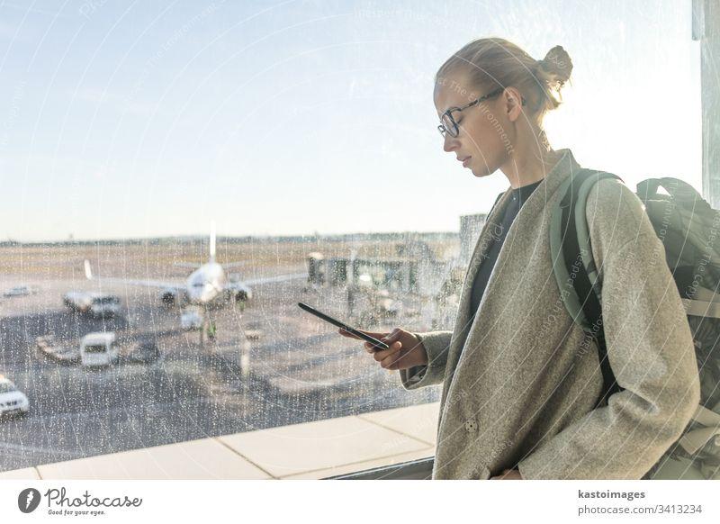 Lässig gekleidete Reisende auf dem Flughafen, die auf ein Smartphone vor den Fenstern des Flughafens mit Blick auf die Flugzeuge auf der Startbahn schaut reisen