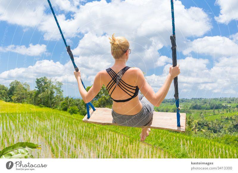 Eine glückliche Reisende, die auf einer Holzschaukel schaukelt und ihren Sommerurlaub inmitten unberührter grüner Reisterrassen genießt. pendeln Frau frei Natur