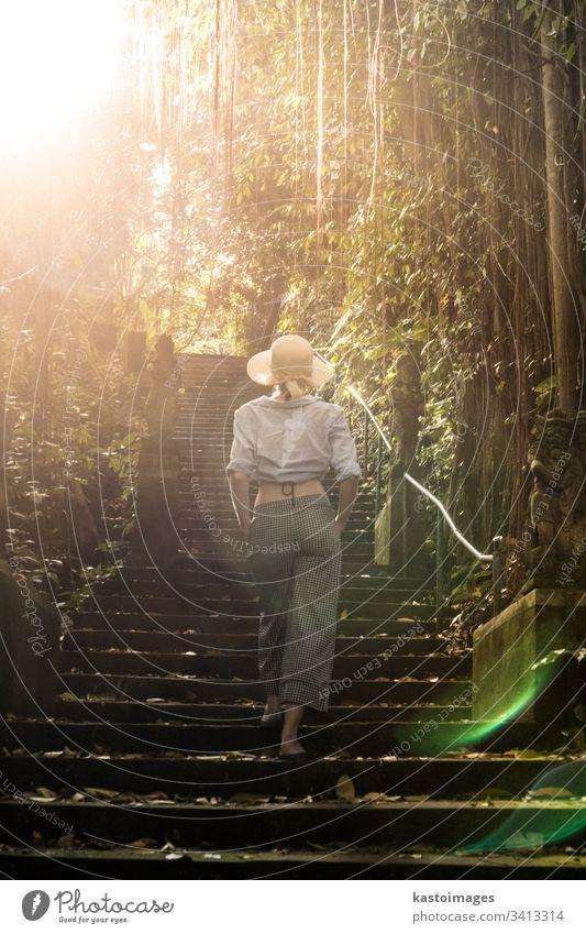 Rückansicht einer schönen, modischen, stilvollen Reisenden mit Hut, die die Treppe des traditionellen Hidu-Tamples in Ubud auf Bali entlanggeht. Konzept eines Luxusurlaubs, bei dem die Welt erkundet und entdeckt wird.