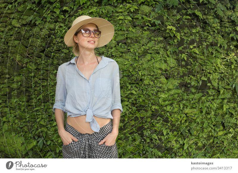 Porträt einer schönen Reisenden. Lächelnde junge Frau mit Sommerhut und Sonnenbrille, die vor einem üppigen tropischen Pflanzengrün vor dem Hintergrund der Wand steht.