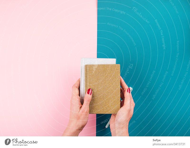 Duotone Hintergrund mit Notizbüchern und Stift Notebook Hände Frau Schönheit Beteiligung rote Maniküre Nägel Planer Hand Schreibwarenhandlung Mode Journal