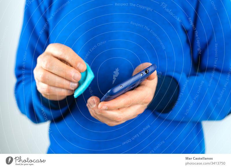 Mann reinigt Handy. Gesundheitsprävention durch Viren. Coronavirus. Covid-19. Sauberkeit covid-19 Virus Bakterien Keime Infektion Pandemie Telefon