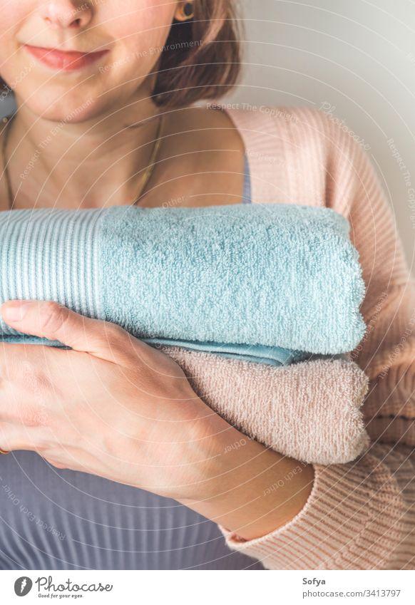 Frau hält saubere gefaltete Handtücher Handtuch Halt Sauberkeit Lächeln Bad gestapelt Pferch zufrieden Spa Glück Hotel Baumwolle sich[Akk] entspannen heiter