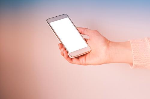 Hand mit Handy-Bildschirm auf rosa und blau Mobile Telefon Hintergrund Smartphone Gerät Korallen Frau Textfreiraum Einladung Anwendung Website Internet