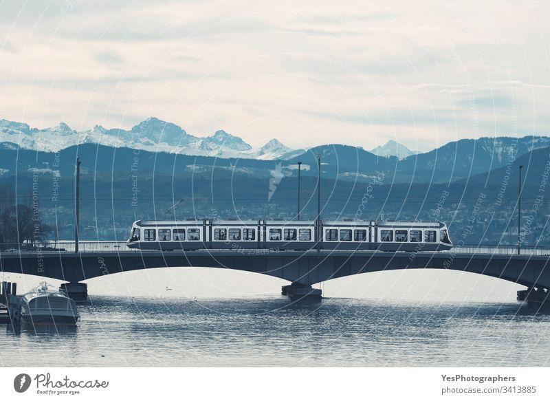 Tram in Zürich auf der Brücke über den See. Skyline der Berge Schweiz Blaue Stunde Stadtrundfahrt Duoton Europa Europäer Landschaft Monochrom Morgen Bergkette