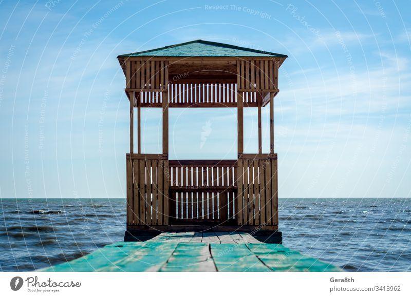 Holzlaube auf dem Hintergrund des Meeres und des blauen Himmels mit Wolken Blauer Himmel Tafeln Gebäude Pavillon Natur alt gemalt Dach MEER Meereslandschaft