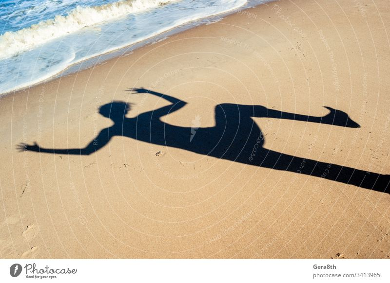 Schatten eines tanzenden Mädchens auf dem Seesand am Strand in der Nähe des Meeres schwarz blau tanzender Schatten Hände ruhen Sand MEER Schatten eines Mädchens