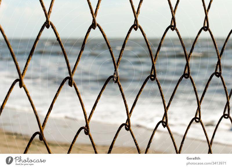 Maschendrahtzaun auf dem Hintergrund des Strandes und des Meeres abstrakt Unschärfe verschwommen Zaun ineinander greifen Natur Wiederholung Rust rostig Sand