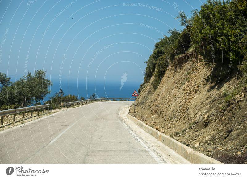 kurvige Küstenstrasse in Albanien die nach rechts abzweigt Straße albanien Kurve Schilder & Markierungen Beton alt Meer roadtrip Büsche Asphalt Linie