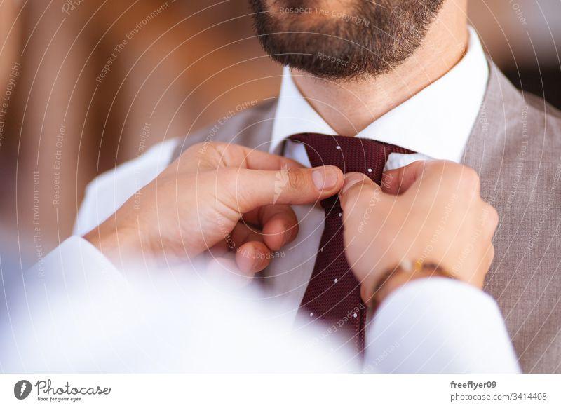 Nahaufnahme von zwei Händen, die einem Bräutigam bei seiner Hochzeit mit der Krawatte helfen Anzug Person männlich Dekoration & Verzierung Tag Weste striegeln