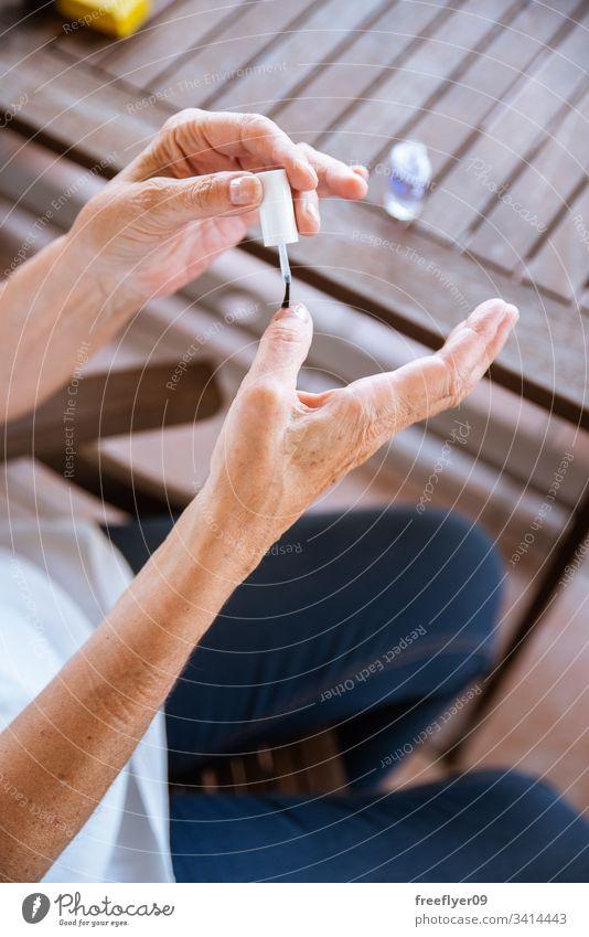 Nahaufnahme einer alten Dame, die ihre Nägel lackiert Menschen Lifestyle Malerei Make-up Bürste Behandlung Schönheit Mode nageln Körper modern Firnis Salon