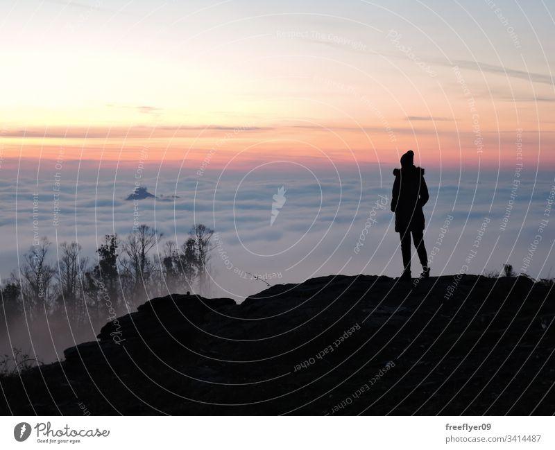 Einsame Wanderin, die vom Gipfel eines Berges aus die Wolken betrachtet einsam allein Frau Wanderer Beanie Hut oben wandern Tourist Tourismus Landschaft Höhe