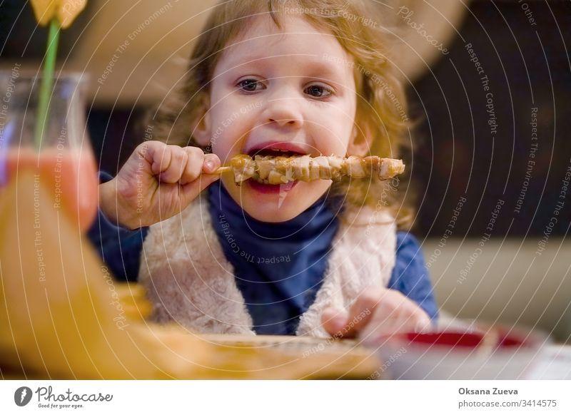 Kleines gelocktes Mädchen isst Hühnchen in einem Cafe bezaubernd Baby Café Kaukasier Kind Kindheit Kinder lockig niedlich lecker Abendessen