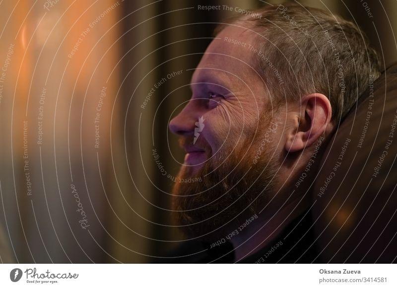 Ein bärtiger Mann schaut fernsehen und lächelt, er sieht glücklich aus. Erwachsener attraktiv Vollbart schön Schönheit lässig Kaukasier bequem kuscheln Tag